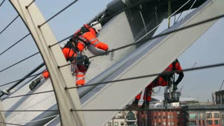 LONDON, UK - NOV 24, 2015: Men in high visibility clothing and harnesses paint the Millennium Bridge