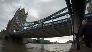 LONDON, UK - OCTOBER 2015: Low angle view panning time lapse clip of Tower Bridge with boats traveling on the Thames