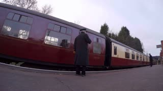 LOUGHBOROUGH, UK - NOVEMBER 21, 2015: Guard blows whistle and vintage train departs Rothley station on Great Central Railway