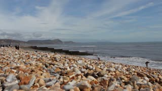 LYME REGIS, UK - APRIL 11, 2016: Tourists on the pebble beach on a sunny spring day