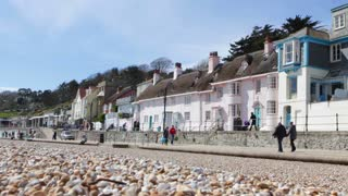 LYME REGIS, UK - APRIL 11, 2016: Tourists walk along the edge of the town's sea front on a sunny spring day
