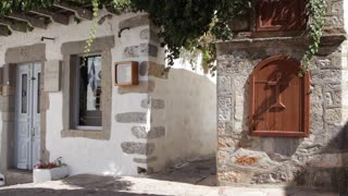 Man in straw hat explores alley in town of Chora on the Greek island of Patmos