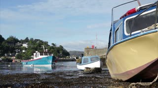 OBAN, SCOTLAND - AUG 29, 2016: Boats rest on the harbour floor when the tide is low