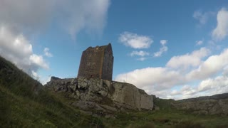 SCOTLAND, UK - OCTOBER, 2015: Time-lapse footage of Scottish Borders castle on a hill. Dramatic clouds float towards the camera at high speed and sun and shade flicker across the landscape.