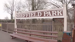 SHEFFIELD PARK, UK - MARCH 19, 2016: Pan to steam engine arriving at Sheffield Park station on The Bluebell Line