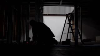 Silhouetted builder uses tape measure and climbs ladder on construction site