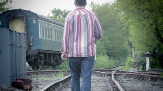 Solitary man walks along a rural railway track