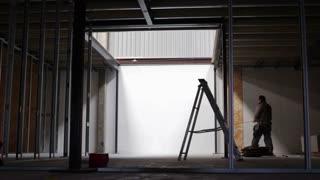 ST ALBANS, UK - APRIL 07, 2016: Builder extends tape measure on construction site