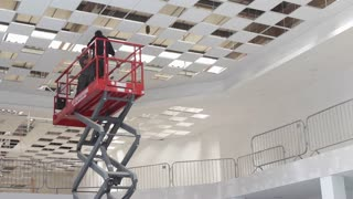 ST ALBANS, UK - JULY 8, 2016: Electricians install ceiling lights using scissor lift in large building