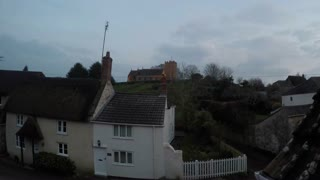 Time-lapse of dusk falling on an English village, revealing floodlit church on hill