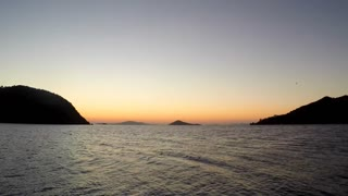 Timelapse boat sails towards the horizon as the sun rises over Greek island of Patmos