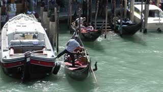 VENICE, ITALY - AUGUST 2012: A gondolier docks his gondola on the Grand canal, filmed from the Rialto bridge
