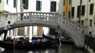 VENICE, ITALY - AUGUST 2012: Gondolier sails gondola under a bridge