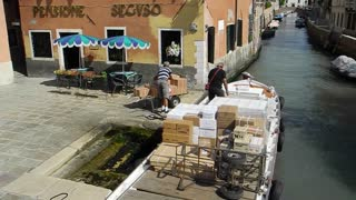 VENICE, ITALY - AUGUST 2012:  Men unload a boat moored in a canal
