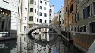 VENICE, ITALY - AUGUST 2012: Woman walks by small venice canal and stands on bridge