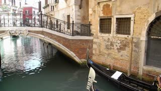 VENICE, ITALY - Gondola goes under a small bridge in a side canal