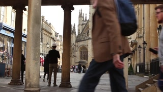 BATH, UK - 10 APRIL 2017:  Tourists and shoppers pass by stone columns leading to a view of Bath Abbey