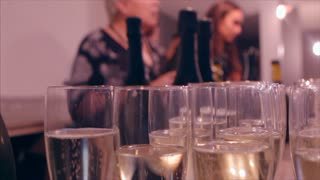 Close-up of fizzy glasses of champagne being filled by bar staff. Focus on foreground glasses.