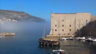 DUBROVNIK, CROATIA - 22 MARCH 2017: Tourist boat in the old town's harbour heads towards sea mist