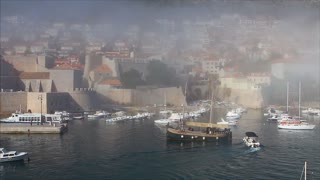 DUBROVNIK, CROATIA - 22 MARCH 2017: Tourist sailing boat arrives in the old town's harbour with sea mist in background
