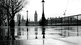 High contrast black and white scene of silhouetted people running by the Thames on a rainy day, with their reflections in a puddle