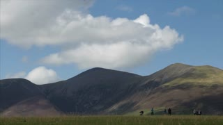 KESWICK, UK - 01 AUGUST 2017:  Tourists enjoy walking and flying a kite in the mountainous English Lake District