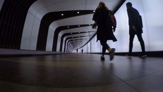 LONDON, UK - 11 MAY 2017: Commuters rush through illuminated tunnel at Kings Cross Railway Station in timelapse sequence