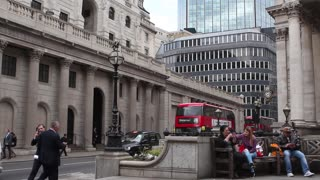 LONDON, UK - 11 MAY 2017:   Iconic red buses pass The bank of England while tourists sit on bench