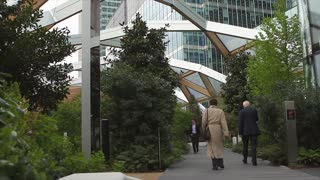 LONDON, UK - 12 APRIL 2017:  Business people walk through the interior garden in the Crossrail station at Canary Wharf