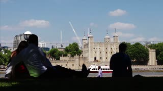 LONDON, UK - 25 MAY 2017:   Silhouetted tourists bask in the shade while sunshine illuminates the Tower of London on a hot sunny day