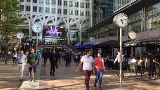 LONDON, UK - 25 MAY 2017:   Tourists walk in slow motion passed the clocks at Canary Wharf on a sunny Spring day