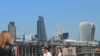 LONDON, UK - 6 MARCH 2017: Tourists walk down the  Southbank of the river Thames on a sunny Spring day, with Millenium Bridge and city towers in background