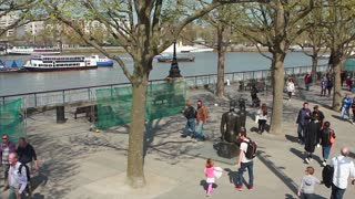 LONDON, UK - 6 MARCH 2017: Tourists walk down the tree lined Southbank of the river Thames on a sunny Spring day