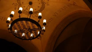 A gothic light fitting sways in the wind under a monstery's arched roof at night