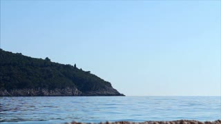 Old fashioned sailing boat floats passed an island in the Adriatic sea off the coast of Dubrovnik