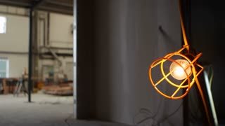 Pull focus from an industrial light bulb in cage to background construction site
