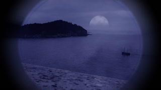 Sailing ship viewed through a handheld telescope at dusk as the moon rises