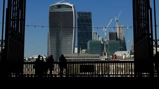 Silhouetted tourists walk down the Southbank of the river Thames on a sunny Spring day, with city towers in background
