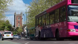 ST ALBANS, UK - 18 APRIL 2017:  Buses drive through high street street with St Peters Church in background