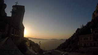 The sun rises behind the misty Spanish hills and the silhouetted monastery of Montserrat in this timelapse clip