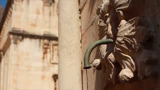 Water pours from pipe in an ornamental stone fountain in Dubrovnik's old city
