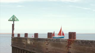 WELLS NEXT THE SEA, UK - 28 MAY 2017: Yacht sails passed a wooden groyne on the open sea