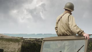 World War 2 American soldier stands in his jeep as Spitfires fly past on the beaches of Normandy
