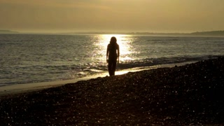 Woman walks on beach (towards camera), silhouetted against the sunset