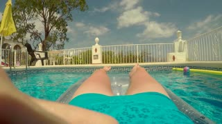 Woman floating in pool on inflatable lilo (POV shot)