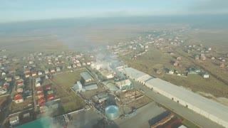 Aerial View Of Factory, Plant. Fly In To Focus On Smoke Rising From The Plant