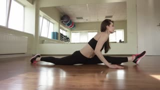 Athletic girl is at a gym. Exercises with the gym equipment