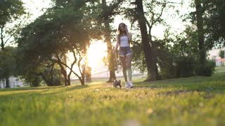 Beautiful Girl Walking With Her Small Dog In The City Park And Using Smartphone.