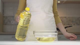 Close-up View Pours Oil. Woman Pours Oil Into A Transparent Bowl.