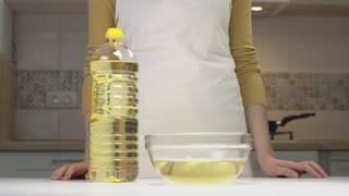 Close-up View Pours Oil. Woman Pours Oil Into A Transparent Bowl